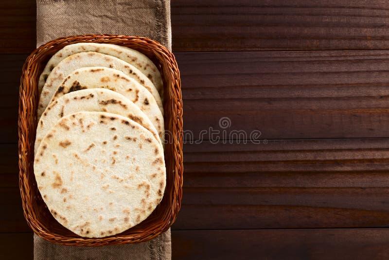 Homemade Indian Naan Bread. Homemade leavened Indian Naan flatbread in basket, photographed overhead on dark wood stock photos