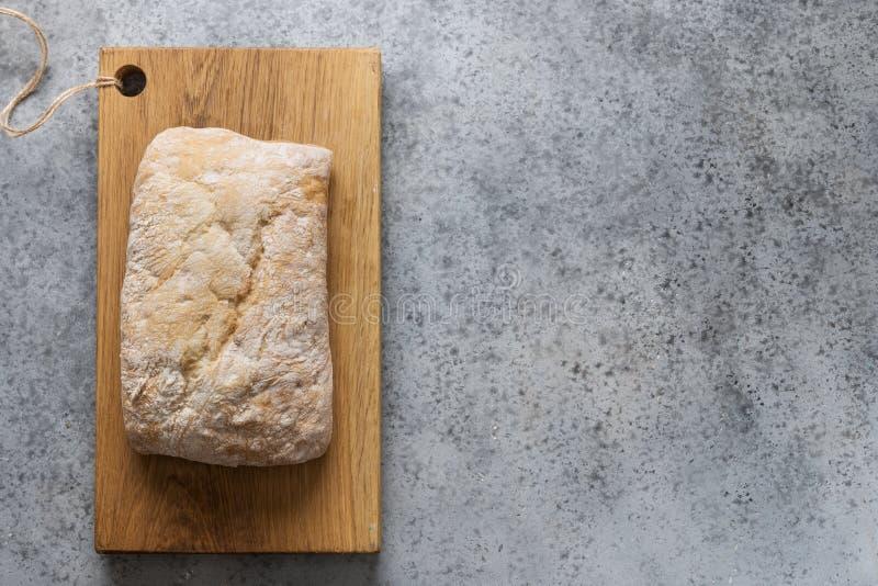Homemade Italian fresh ciabatta bread on chopping board. Top view, copy space stock photography