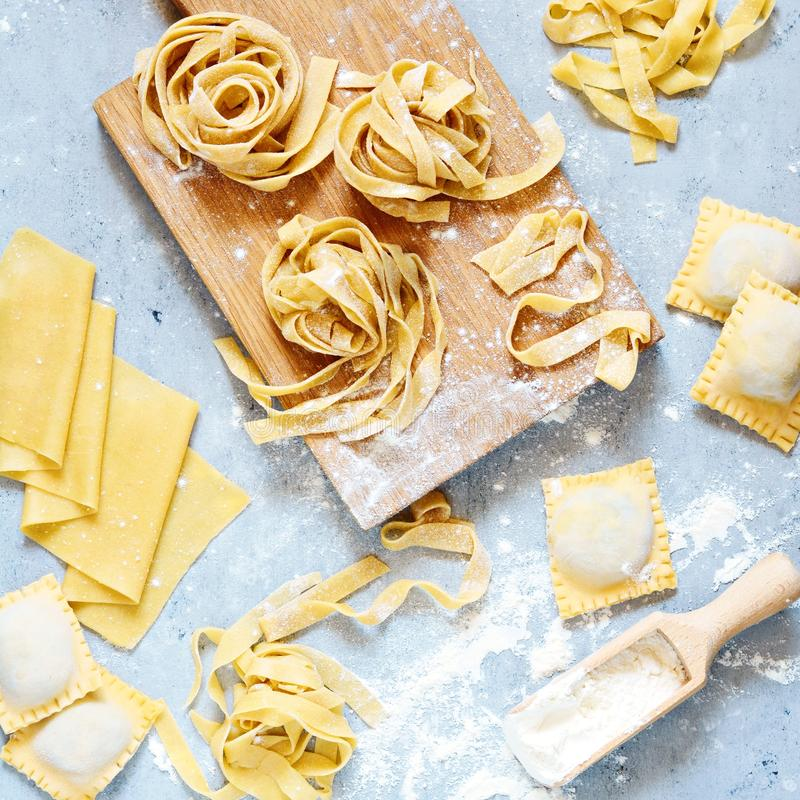 Homemade italian pasta, ravioli, fettuccine, tagliatelle on a wooden board and on a blue background. The cooking process royalty free stock image