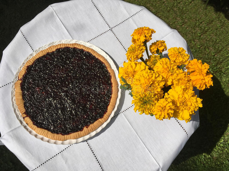 Homemade jam tart on a garden table with bouquet of flowers royalty free stock image