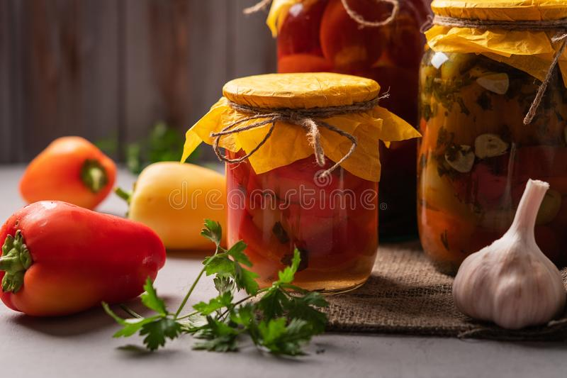 Homemade jars of pickled peppers and tomatoes on a rustic wooden background. Pickled and canned product. Next. Ingredients for cooking. Close-up royalty free stock images
