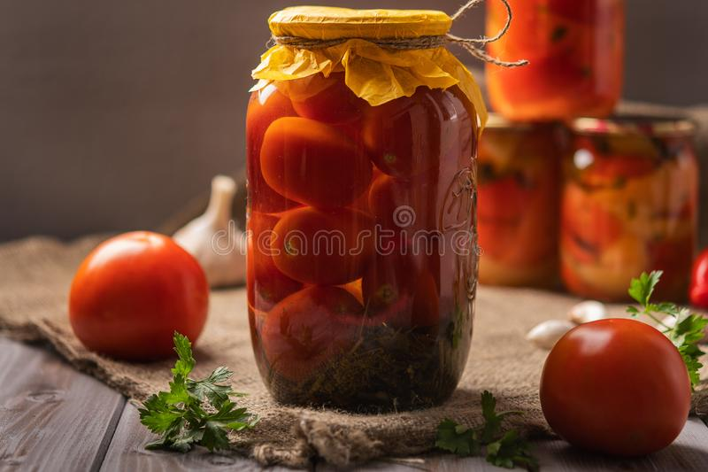 Homemade jars of pickled tomatoes on a rustic wooden background. Pickled and canned product. Next tomatoes and other for. Cooking. Close-up stock photography