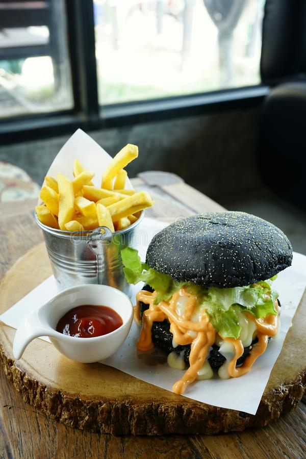 Homemade juicy black burger and French fried on wooden table. With window lighting royalty free stock photography