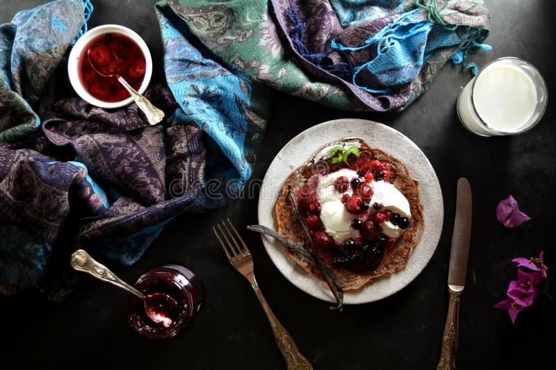 Keto Chocolate Pancakes with Whipped Cream and Berries. Homemade ketogenic diet pancakes with whipped cream and berries on black background stock photography