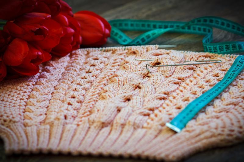 Homemade knitting pink pullover. With needles and tulips for decoration royalty free stock photo