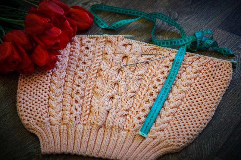 Homemade knitting pink pullover. With needles and tulips for decoration royalty free stock photos