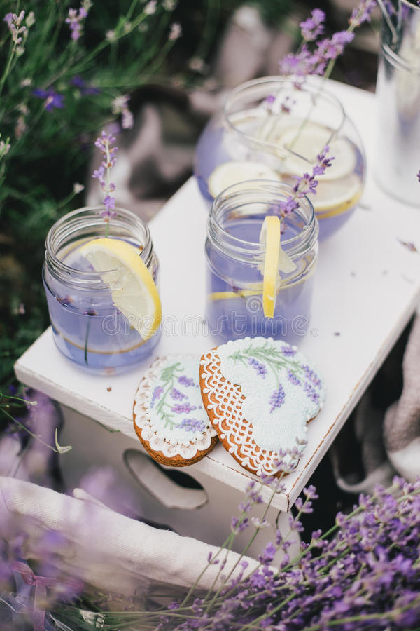 Homemade lavender lemonade with fresh lemons on a white wooden tray. In a lavender field royalty free stock photography