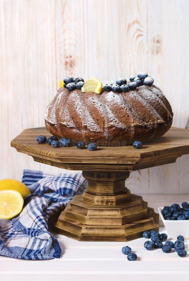 Homemade lemon bundt cake on wooden stand. stock image