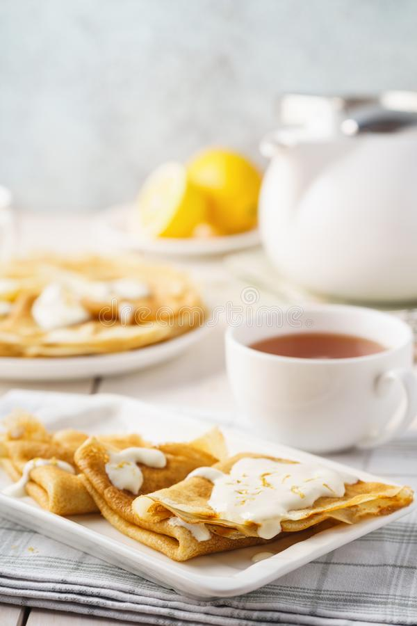 Homemade lemon crepes or blini with creamy sauce. And tea stock photos