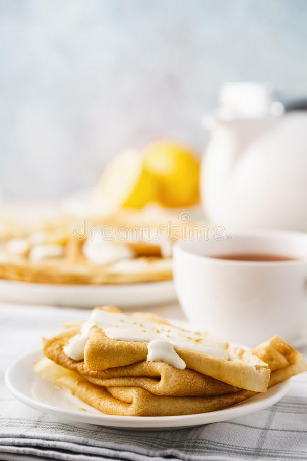 Homemade lemon crepes with custard sauce and tea. Traditional pastry stock photography
