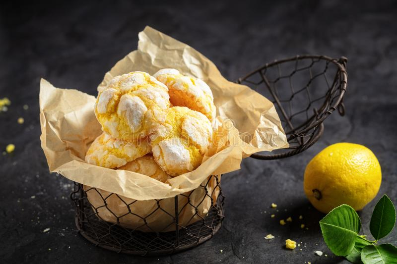 Homemade lemon crinkle cookies with powdered sugar icing on back. Ing paper in small metal backed , on dark background stock photos