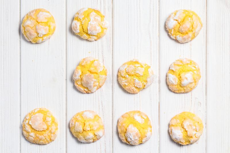 Homemade lemon crinkle cookies with powdered sugar icing. Cracked citrus biscuits on white wooden background, top view.  stock images