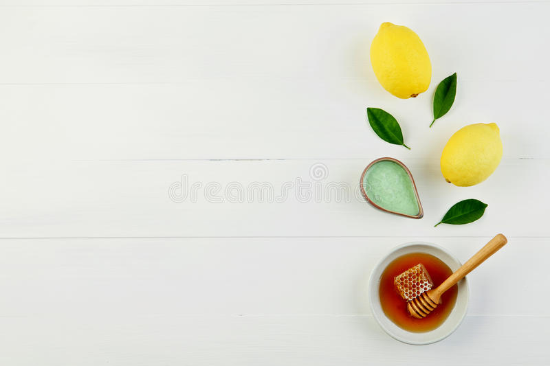 Homemade lemon salt bath and fresh honey in the plate with honey. Comb and wooden dipper on rustic white background from top view. Flat lay good for background royalty free stock images