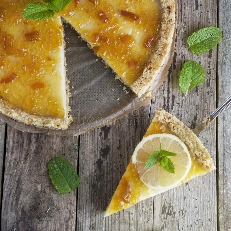 Homemade lemon tart. Sweet citrus dessert with mint leaves anc jelly cream. Rustic wooden background. Square iamge. stock photo