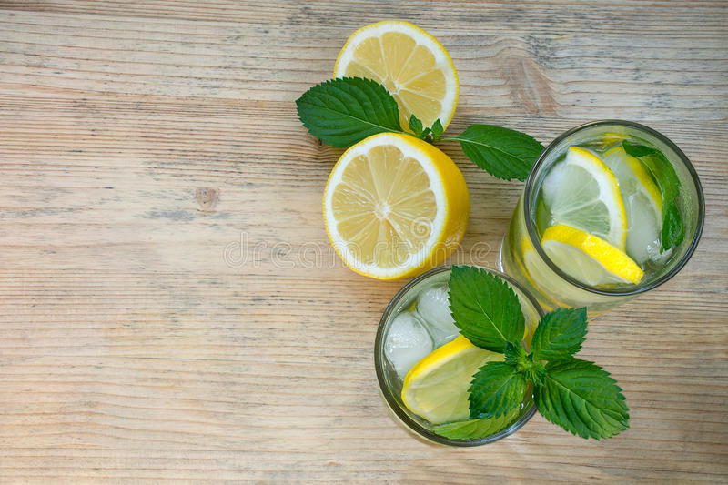 Homemade lemonade with ice in glasses on a wooden background. Water with lemon, mint and ice. Health concept. Copy space. Homemade lemonade with ice in glasses stock images