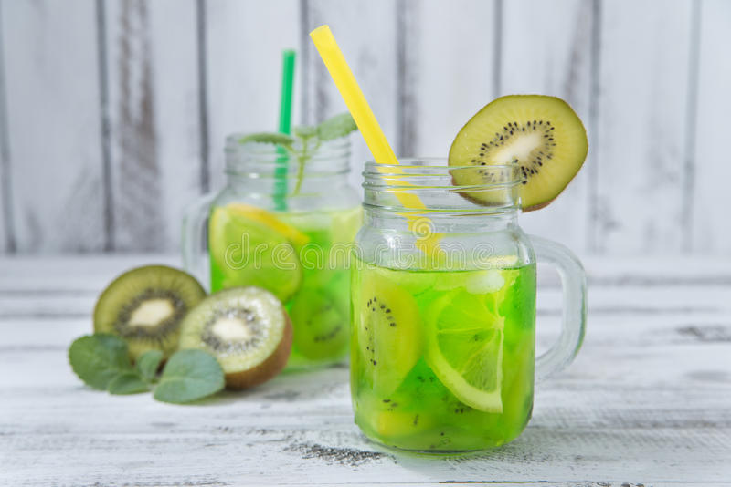 Homemade lemonade with kiwi. Lemon, mint in glass on a wooden rustic table stock images