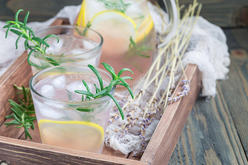 Homemade lemonade with lavender, fresh lemons and rosemary on wooden background, horizontal, copy space. Homemade lemonade with lavender, fresh lemons and royalty free stock images