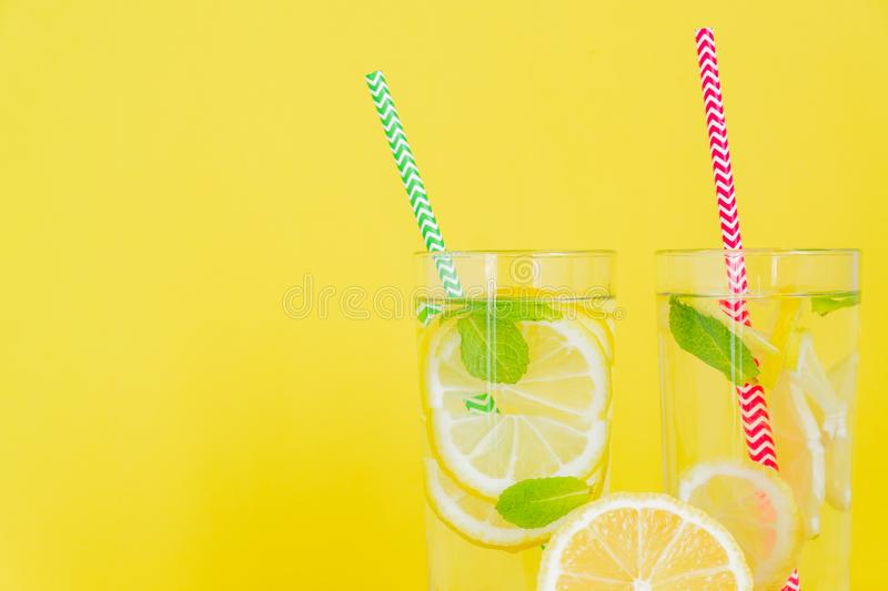 Homemade lemonade with lemon and mint on colored yellow background. Summer cold drink cocktail. Copyspace stock photography