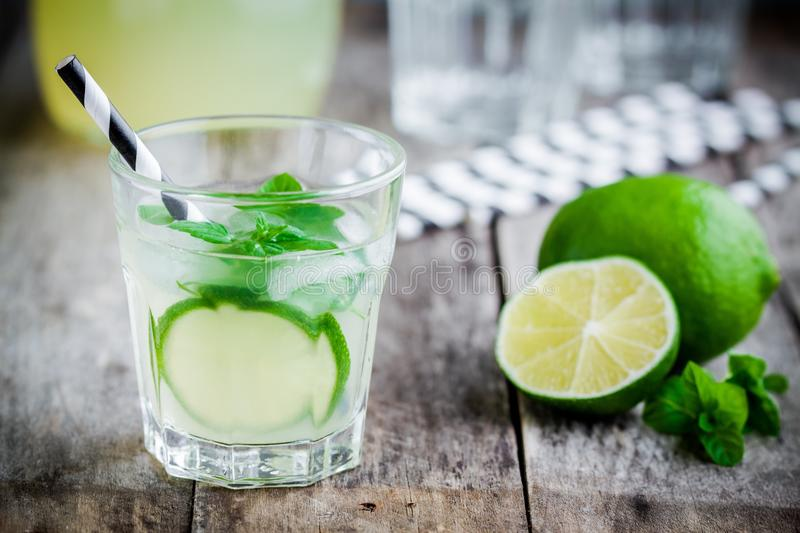 Homemade lemonade with lime, mint and ice on a wooden table. Homemade lemonade with lime, mint and ice on a rustic wooden table royalty free stock photography