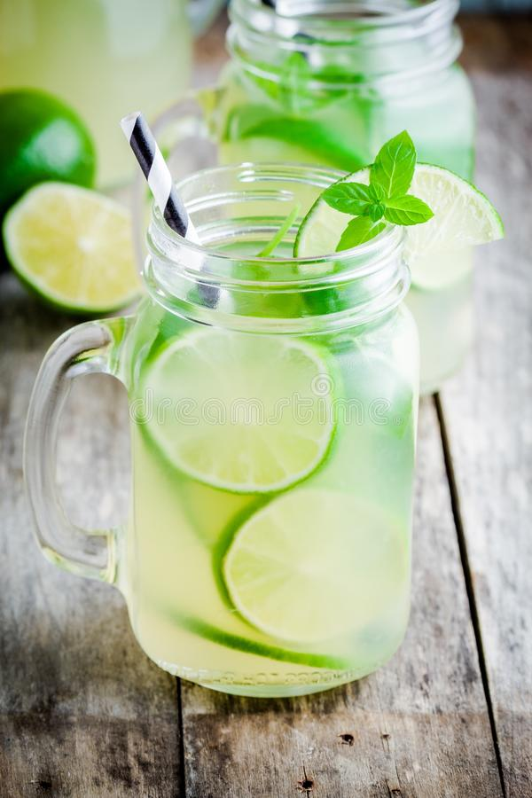 Homemade lemonade with lime, mint in a mason jar on a wooden table. Homemade lemonade with lime, mint in a mason jar on a wooden rustic table stock photos