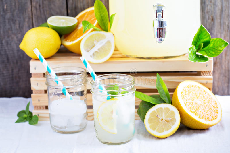 Homemade lemonade in mason jars. Homemade lemonade in beverage dispencer and mason jars stock photo