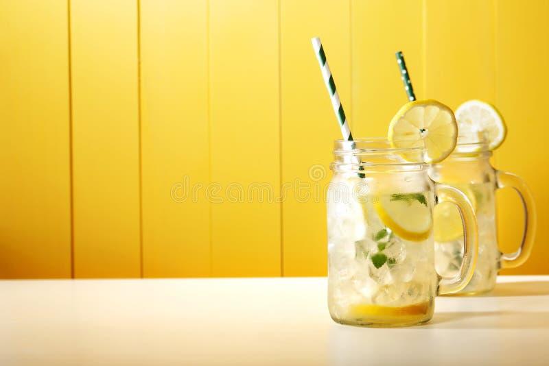 Homemade lemonade in mason jars. With big green paper straw stock photos