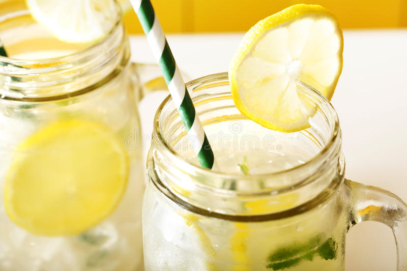 Homemade lemonade in mason jars. With big green paper straw stock images