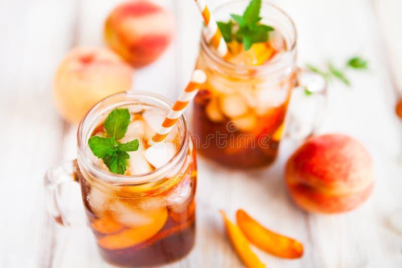 Homemade lemonade with ripe peaches and fresh mint. Fresh peach. Homemade iced lemonade with ripe peaches and fresh mint. Fresh peach ice tea in a mason jar stock image