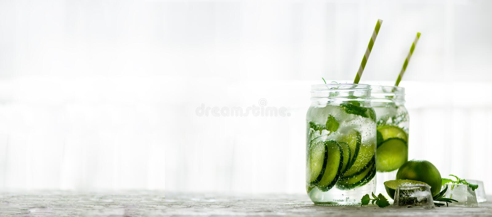 Homemade lime lemonade with cucumber, rosemary and ice, white background. Cold beverage for hot summer day. Copyspace stock image