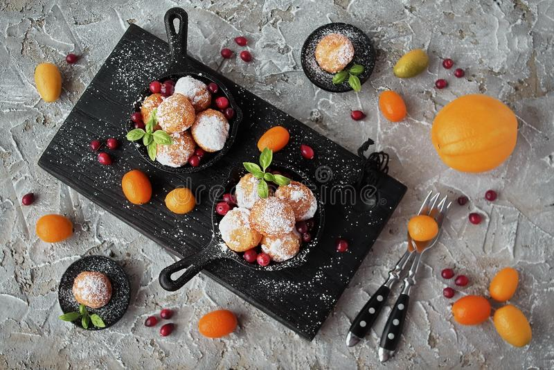 Homemade little donuts of sweet cottage cheese in a cast iron skillet stock photos