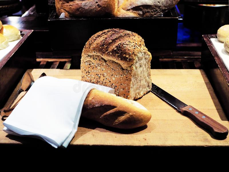 Homemade loaf of whole grain bread and French Baguette with knife on wooden board. Mostly served with butter or jam. stock image