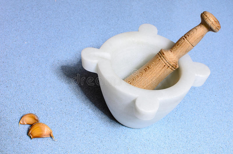 A homemade marble's pestle over a blue silestone desk with garlic stock images