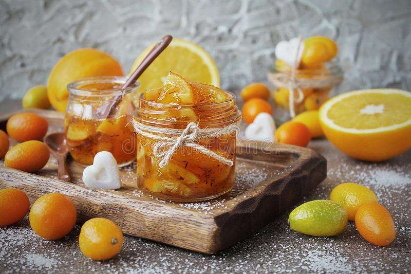 Homemade marmalade from oranges in glass jar. Homemade marmalade from oranges in a glass jar, fresh orange and kumquats on a gray granite background royalty free stock photo