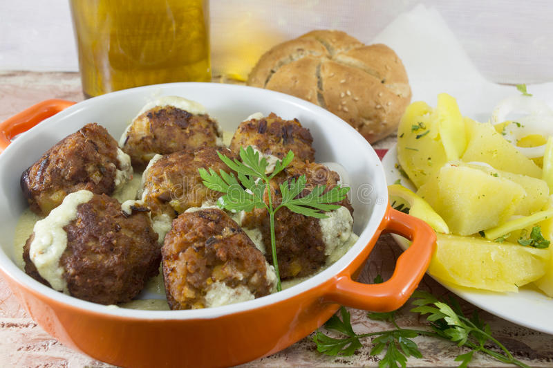 Homemade meatballs served in an orange bowl with corn bread, pot royalty free stock photos