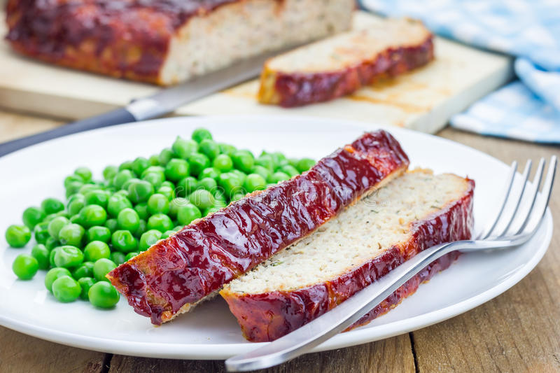 Homemade meatloaf garnished with green peas. On a white plate royalty free stock photos