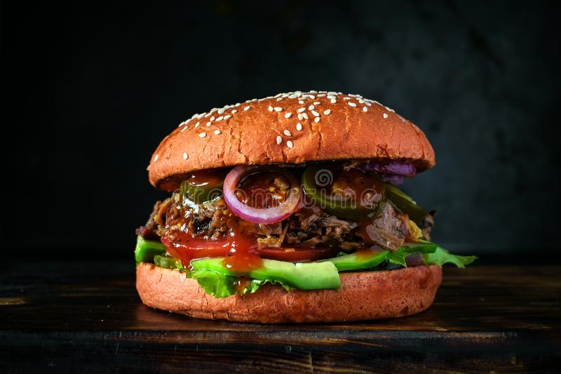 Homemade Mediterranean Burger with beef brisket, olives, onion, avocado and Tabasco stock image