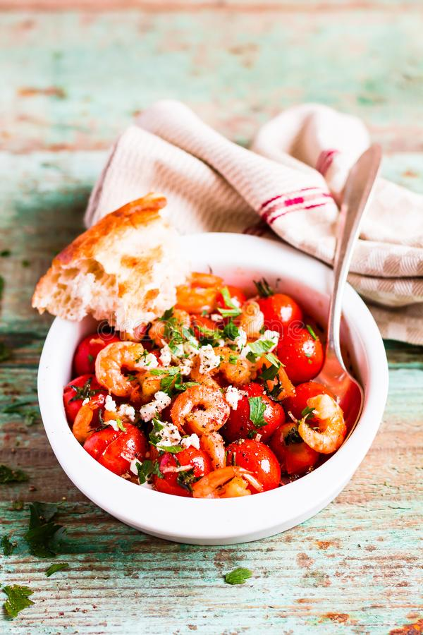 Homemade mediterranean meal with roasted cherry tomatoes, prawns or shrimps, fresh salted feta cheese, parsley served with freshly royalty free stock images