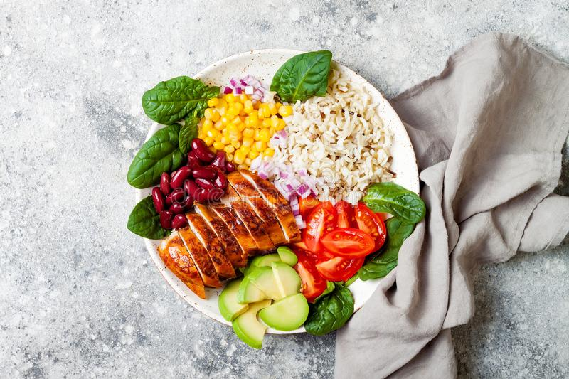Homemade Mexican chicken burrito bowl with rice, beans, corn, tomato, avocado, spinach. Taco salad lunch bowl. stock image