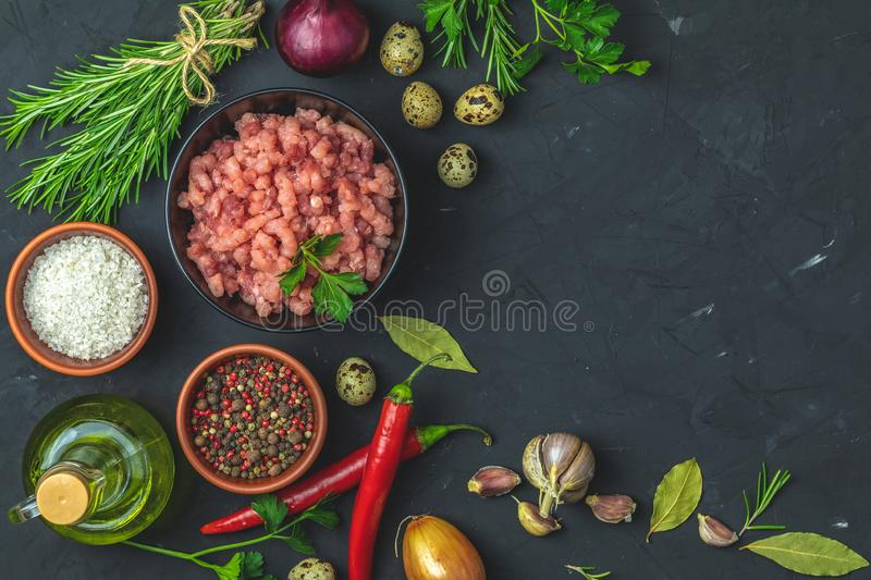 Homemade minced meat in a black bowl with ingredients for making royalty free stock photo