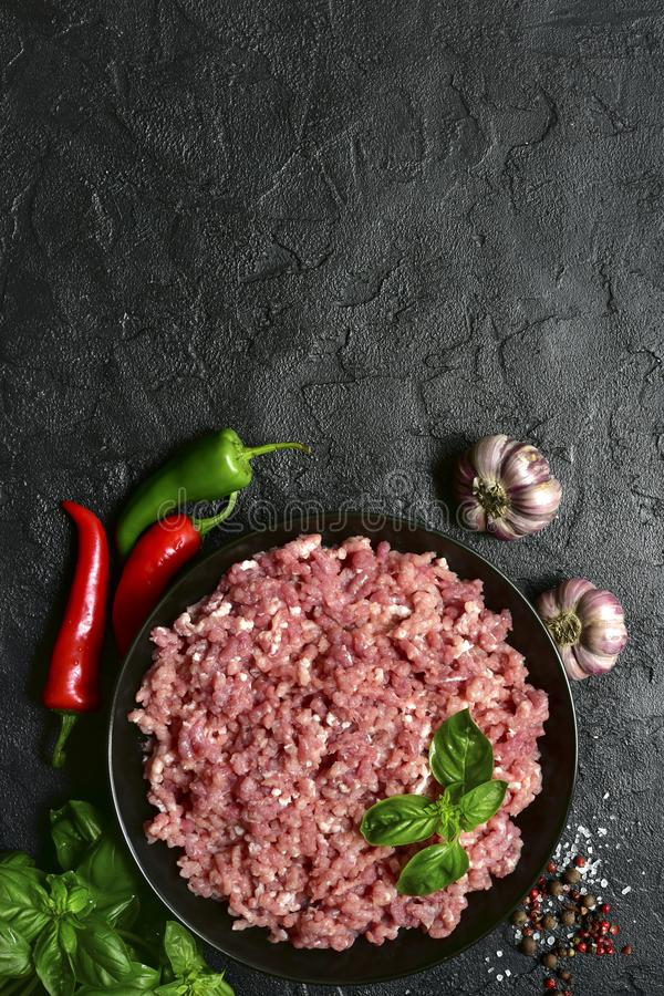 Homemade minced meat in a black bowl over dark slate, stone or concrete background with ingredients for making.Top view with copy royalty free stock photo