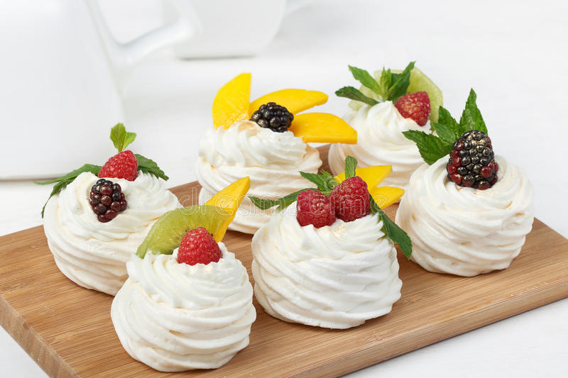 Homemade mini pavlova cakes with whipped cream and fresh berries royalty free stock photos