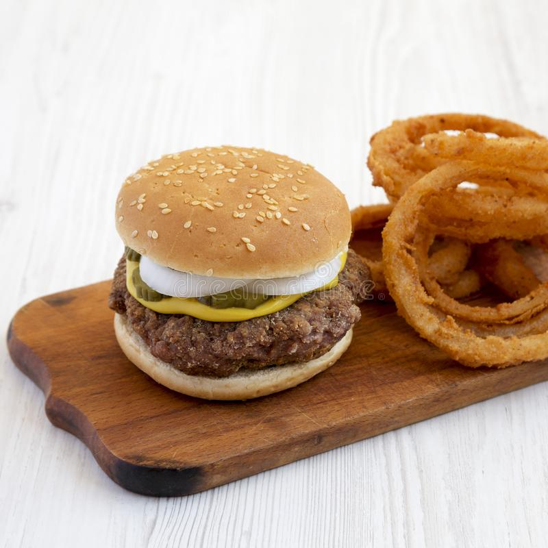 Homemade Mississippi Slug Burger with onion rings on a rustic board on a white wooden surface, low angle view. Closeup.  stock photo