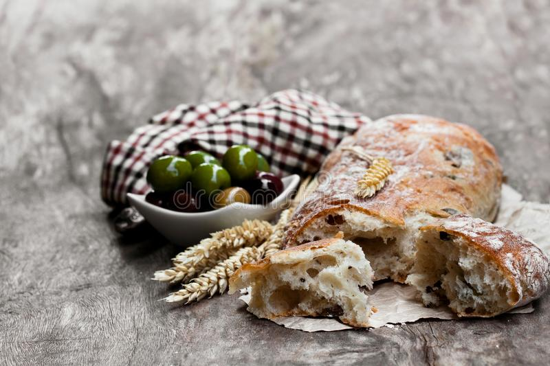 Homemade mixed olive ciabatta on rustic wooden table stock photo