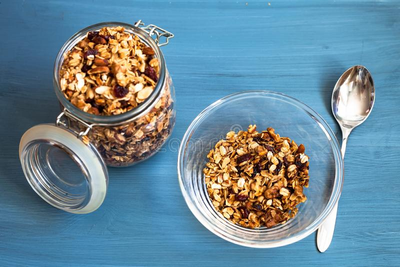 Homemade muesli in a plate on a blue background, healthy breakfast of oatmeal muesli, nuts, seeds and dried fruits royalty free stock photography