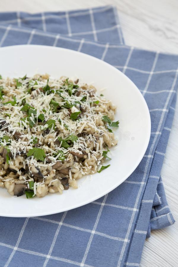 Homemade mushroom risotto with parsley on a white plate, low angle view. Closeup.  stock photography