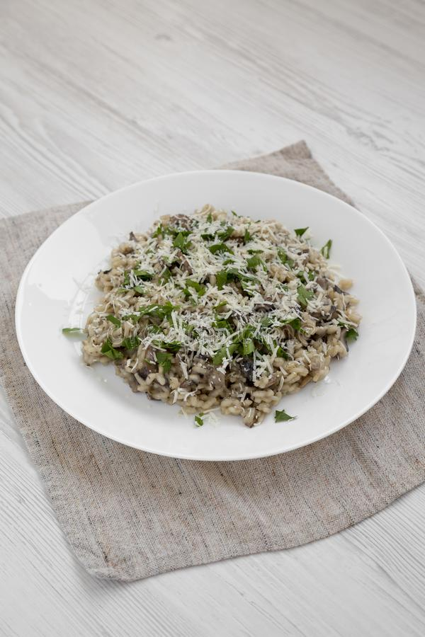Homemade mushroom risotto with parsley on a white plate on a white wooden background, side view. Closeup stock photography