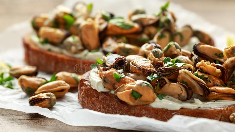 Homemade Mussels on grilled bruschetta, toast with soft cheese and herbs stock image