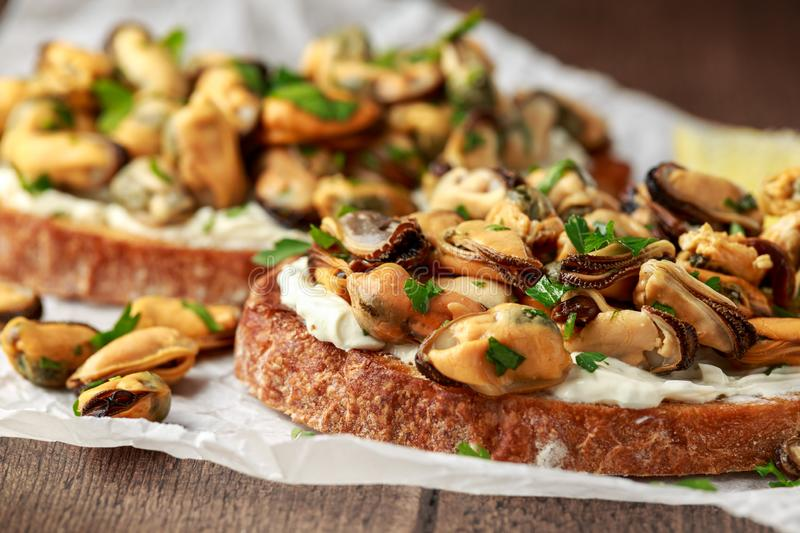 Homemade Mussels on grilled bruschetta, toast with soft cheese and herbs stock images
