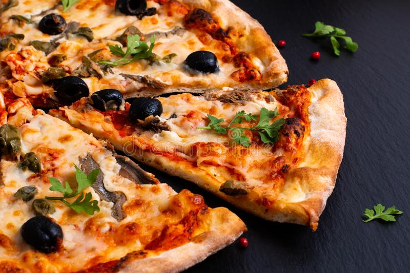 Homemade Napoli Pizza or anchovies pizza on black slate stone. Food Homemade Napoli Pizza or anchovies pizza on black slate stone stock images