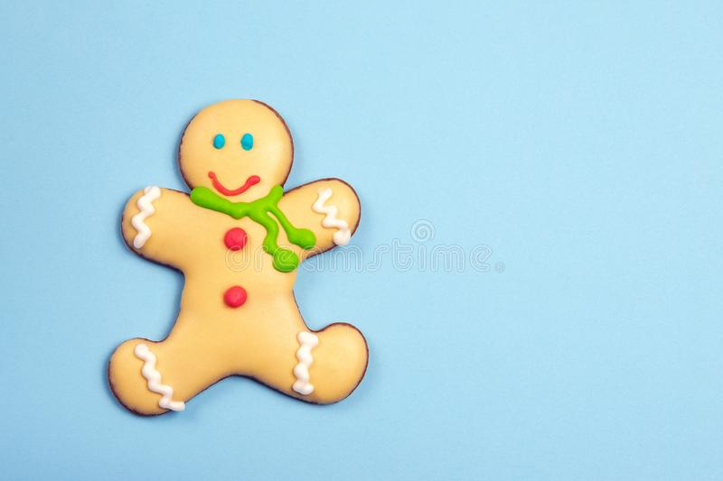 Homemade natural gingerbread man cookie in scarf on light blue paper background. Traditional winter holidays christmas. And new year sweet dessert. Copyspace royalty free stock photo
